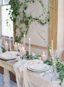 romantic and whimsical table settings with trailing vines and neutral toned candles
