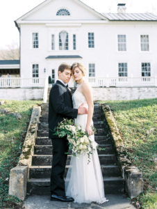 Bride and groom portrait with architecture and bridal bouquet