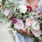 Bride in blue gown with oversized bridal bouquet for summer garden wedding