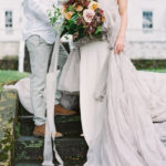 bride and groom engagement portraits with over sized organic bouquet