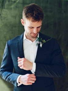 Groom with boutonniere portrait with velvet backdrop