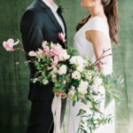 bride and groom with bouquet with velvet backdrop at intimate elopement