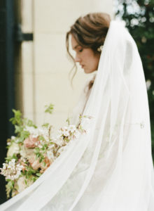 feminine luxe bridal style with veil and lush, organic spring bouquet