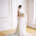 Parisian femininity bridal style with oversized bouquet and veil